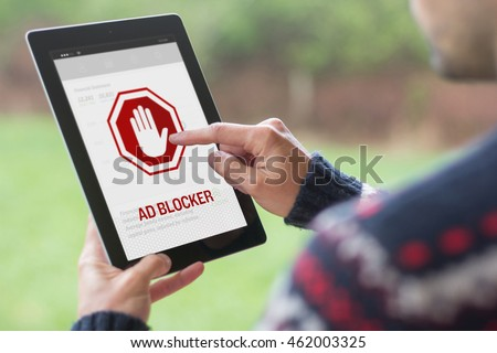 A young man is using his tablet in a green nature background, with ad blocker on the screen #462003325