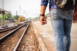A young man is walking, holding a bottle of water at the train station.
