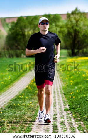 a young man jogging through the fields