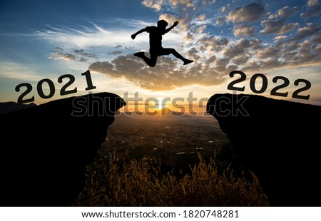 A young man jump between 2021 and 2022 years over the sun and through on the gap of hill  silhouette evening colorful sky. happy new year 2021.