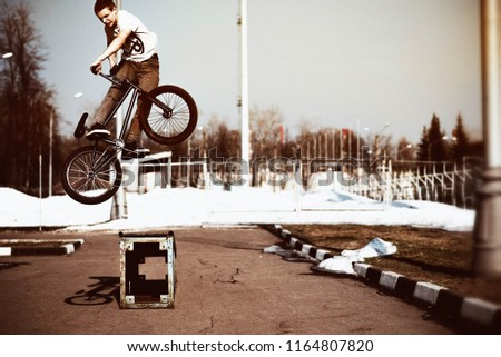 a young man jumps on a bicycle #1164807820