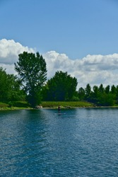 A young man kayaking in a river going to an island full of trees, saint Laurent river, rapides park, Montreal, QC, Canada