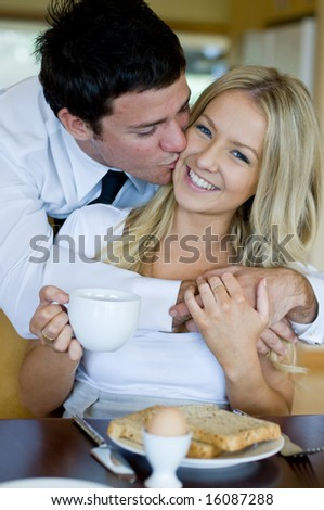 A young man kisses his wife whilst she is sat having breakfast
