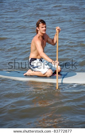A young man kneels on his stand-up paddle-board