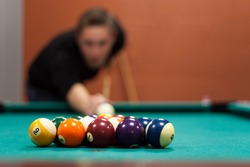 A young man lines up his shot as he breaks the balls for the start of a game of billiards. Shallow depth of field.