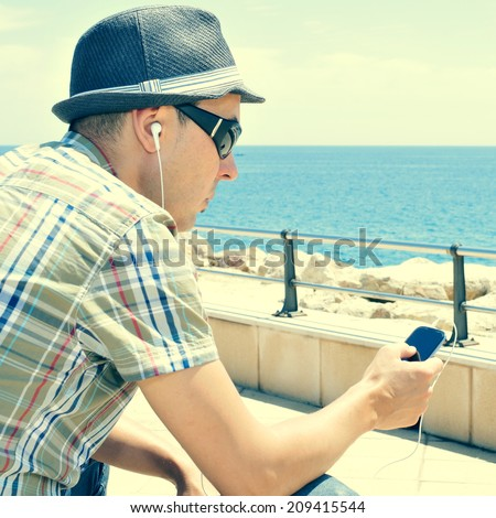 a young man listening to music or talking with headphones in a smartphone outdoors, filtered