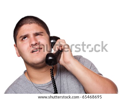 A young man listens on the telephone with an annoyed expression on his face.