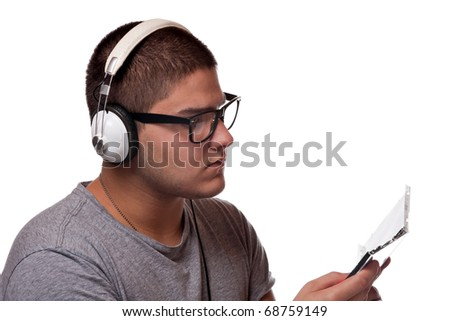 A young man listens to music with a set of head phones while examining the album cd case.
