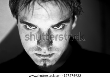 A young man looking angry at the camera..High contrast, hard light and shadow, desaturated colors, soft focus