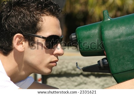 A young man  looking through a telescope