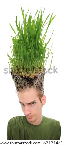 A young man looking upward at the grass growing from the roots on top of his head. This concept can apply to environmentalists, farmers, agriculture, landscapists, gardeners, and crazy haircuts.