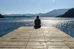 A young man looks into Lugu Lake from wooden platform, surrounded by mountains and sun reflections on the water
