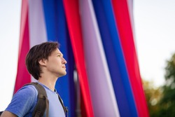 A young man looks to the future against the background of the Russian flag patriot. Russian flag independence day constitution. Russian Federation. 12 June. August 22. November 4th. Citizen. Tricolor