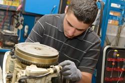 A young man mechanic repairing  motor boats