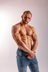 A young Man of strong constitution with a relief figure of a bodybuilder with a beautiful torso. Shooting in the studio on a white background.