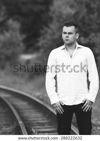 a young man on a railway line black and white photography