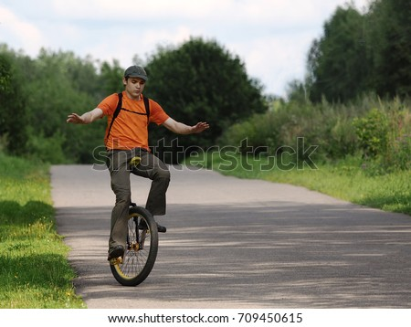 a young man on a unicycle performs slower  on an asphalt rural road on a summer day