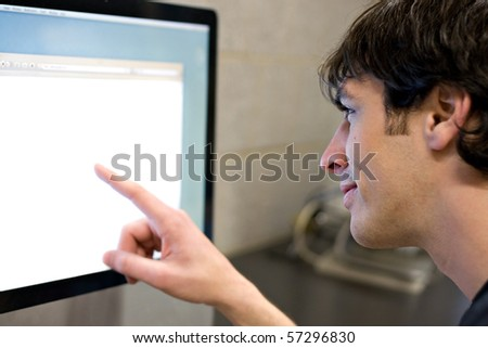 A young man pointing at a modern computer monitor lcd with copy-space.  Shallow depth of field with strongest focus on the face.