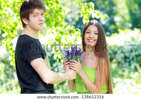 A young man presenting blue flowers to a woman on a summer day. Focus on woman face