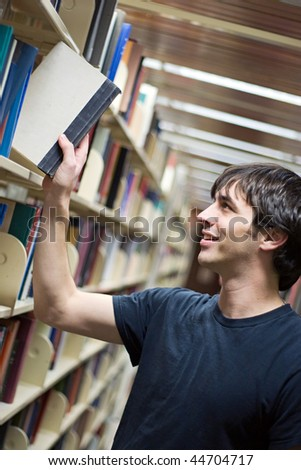 A young man pulling a book from the shelf at the library.