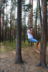 a young man pulls himself up on one arm on a horizontal bar in the woods