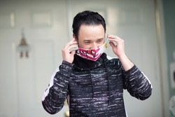 A young man putting on his face mask when getting out of his house. The government advises people to wear cloth masks to protect themselves from covid-19 pandemic.