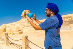 A young man putting on the mask facing the Great Sphinx of Giza and the Pyramids of Giza in the background, tourism in the middle of the coronavirus pandemic, covid-19. In the city of Cairo, Egypt