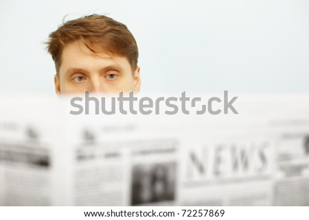A young man reads the news in the newspaper