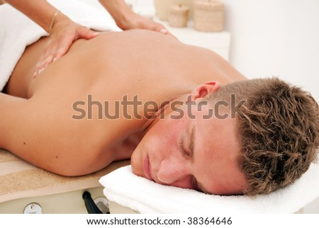 A young man relaxes as he enjoys a luxurious spa treatment from a female masseuse.