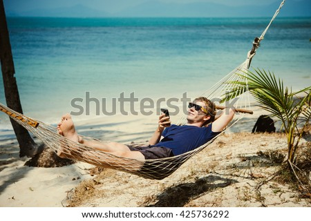 A young man relaxes in a hammock at the beach while checking messages on his smartphone. Toned image