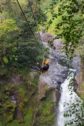 A young man riding on a zip line rope in an extreme adventure jungle in Xico, Veracruz, Mexico