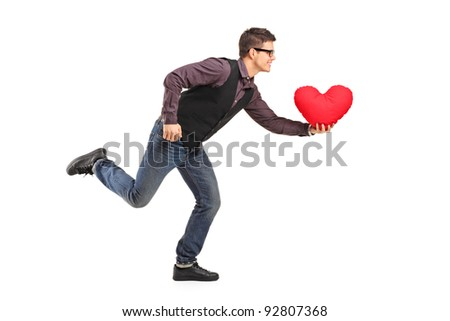 A young man running with a red heart shaped pillow in his hand isolated on white background