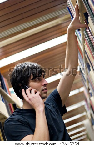 A young man searching for a book or topic at the library while doing research of some sort.