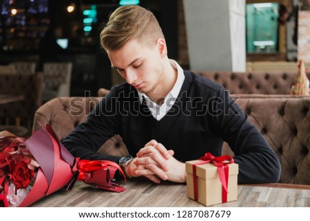 A young man sits in a restaurant and is waiting for a meeting with a girlfriend, girlfriend or wife. Flowers and a gift are near, looking at the clock. Romantic date, Valentine's Day. #1287087679