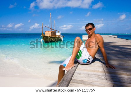 A young man sits on a pier