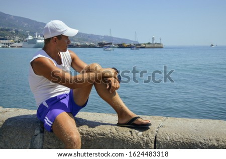 A young man sits on the waterfront and enjoying the view of the sea. Handsome boy is sitting on stone and looks at ships and boats in the water of the ocean. Port city on the background