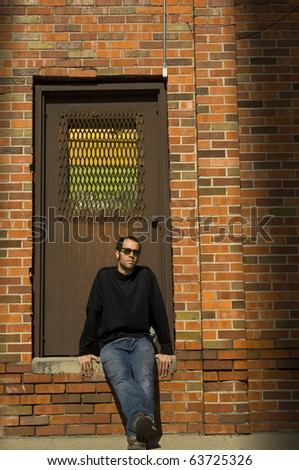 A young man sitting in an illuminated doorway of a brick building