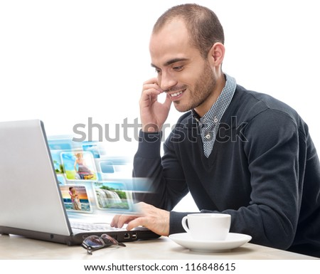 A young man sitting in front of a laptop and sharing photo and video files in social media resources using his computer isolated