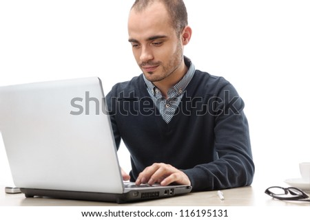 A young man sitting in front of a laptop isolated