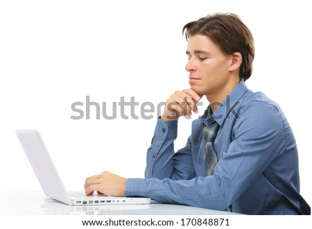 A young man sitting in front of a laptop, isolated on white