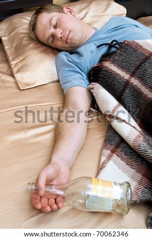 A young man sleeping on the couch with a bottle of whiskey