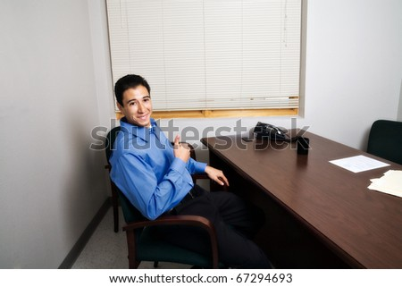 a young man smiles and gives a thumbs up while preparing to be interviewed for a job (or in a meeting with the boss, etc)