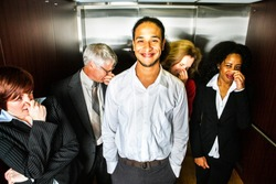 A young man smiles in embarrassment in an elevator while people hold their noses.