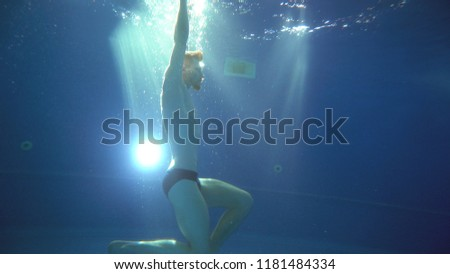 A young man somersaults and does a somersault under the water. He is posing in front of the camera. Underwater view. #1181484334