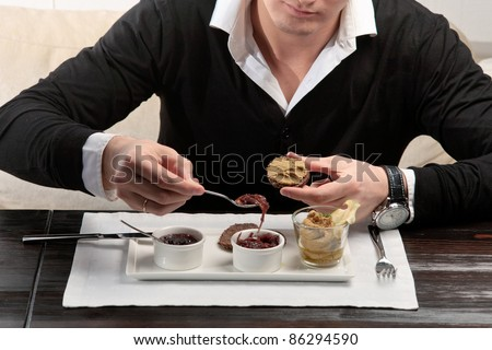 A young man spreading cherry jam on a piece of bread, sitting at an elegantly served table in a restaurant