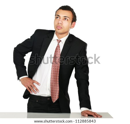 A young man standing near desk, isolated on white background