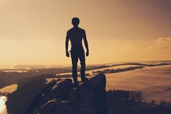 A young man stands on top of the mountains at sunset