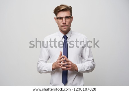 A young man stands with his fingers folded in front, looks through glasses, a little nerdy, tense, tries to make a choice or find a problem decision, on a white background