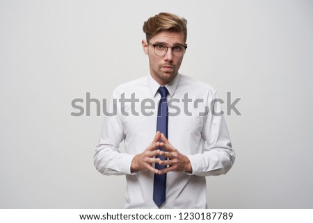 A young man stands with his fingers folded in front, talking to his boss, giving him a report or presentation. Looks through glasses, a little nerdy, tense, on a white background