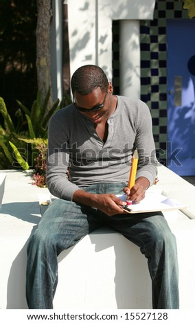 a young man takes notes and erases mistakes on a sheet of paper with a giant pencil - stock photo